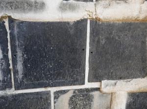 Particolare di muro di kura in cui il namako si è rotto mostrando i buchi dei perni che fissano le piastrelle