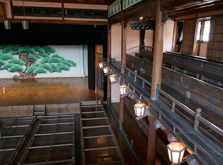 Interno del teatro kabuki di Uchiko con platea e galleria in legno e il tipico sfondo con pino disegnato