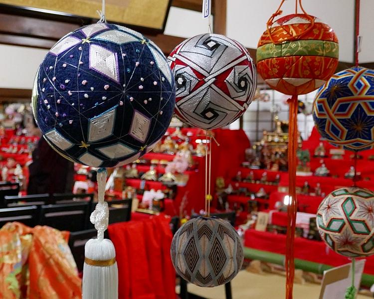 Temari tradizionali con disegni geometrici appese con apparato delle hina sullo sfondo
