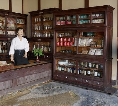 Interno farmacia d'epoca con armadi pieni di bottiglie e pacchi di medicinali e manichino venditore