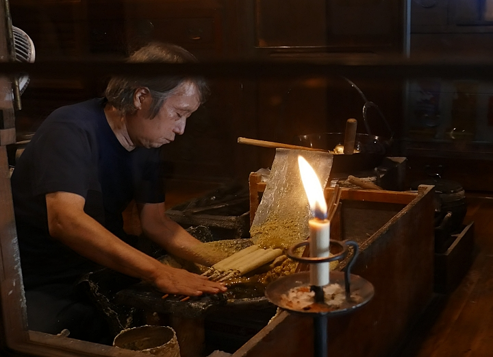 Mastro Omori Artigiano posa cera liquida sulle candele al lume di una fiamma