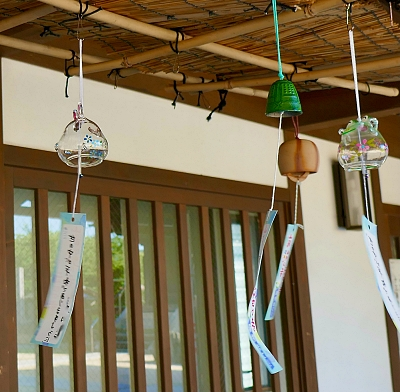 Campanelle di vetro e metallo con striscia di carta appesa al battacchio