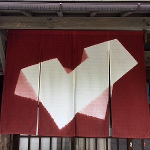 noren disegno geometrico a sfondo mattone