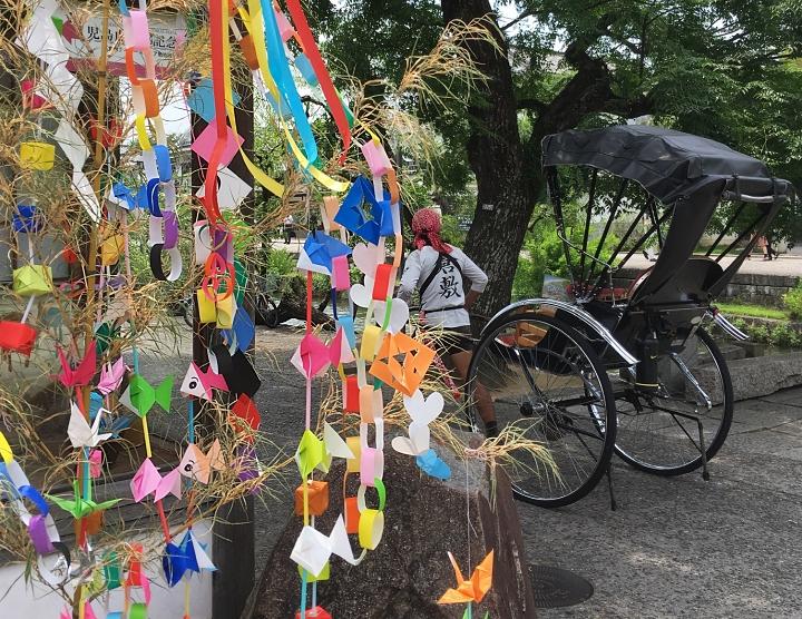 Steli di bambù con decorazioni in carta multicolore per Tanabata. Sullo sfondo portatore di richò