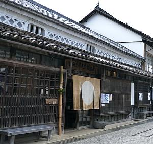 facciata casa tradizionale con koshi in legno e noren con cerchio bianco su sfondo marrone