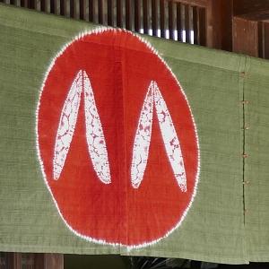 Noren sfondo verde con cerchio rosso e dentro particolare di zori