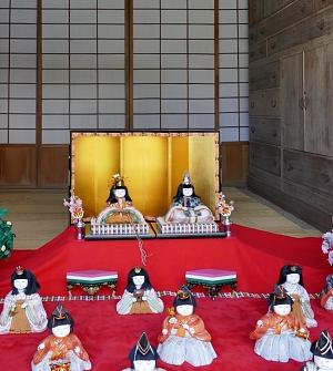kimekomi hina su tappeto rosso e davanti a un paravento dorato